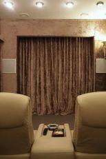 Раздвижная система штор с электрокарнизами ( карнизы с электроприводом) расположена на окне, экране и входе. Шторы для домашнего кинотеатра сшиты из плотного бархата на подкладке. Обивка стен выполнена из того же бархата, как и шторы, кроме этого стены оформлены декоративными панелями, обитыми кожзамом. Бархатные шторы и стены, панели под кожу крокодила, стильные светильники — все детали безупречно соответствуют стилю Арт-деко и превосходно подходят для дизайна домашнего кинотеатра.