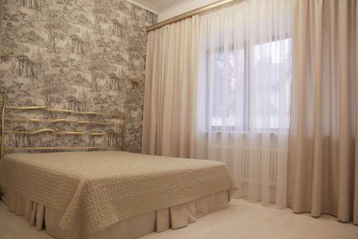 Шторы гостевой спальни для загородного дома. Спальня скорее соответствует стилю эклектика – совмещение основного классического декора с элементами в стиле Прованс, туаль де Жуи и современного. Дизайн штор и интерьера спальни, выполненный в спокойных бежевых тонах, создает ощущение сдержанной роскоши и придется по душе очень многим людям, сделав визит гостей более комфортным. Особенности пошива: подзор для кровати позволяет прикрыть не очень эстетичный низ, даже если покрывало будет снято.
